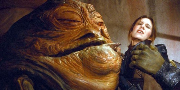 Iconic Photo from the Movie STAR WARS -- Jabba the Hut has Princess Leia in his clutches, and it trying to lick her face with his tongue -- she is, understandably, REPULSED.